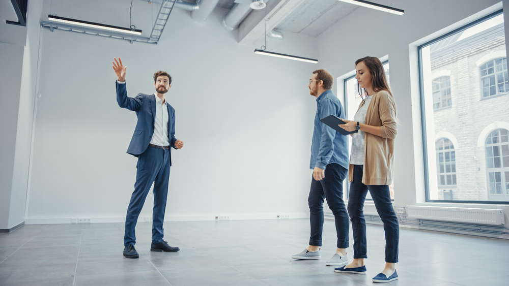 Real Estate Agent Showing a New Empty Office Space to Young Male and Female Hipsters. Entrepreneurs Meet the Broker with a Tablet and Discuss the Facility They Wish to Purchase or Ren