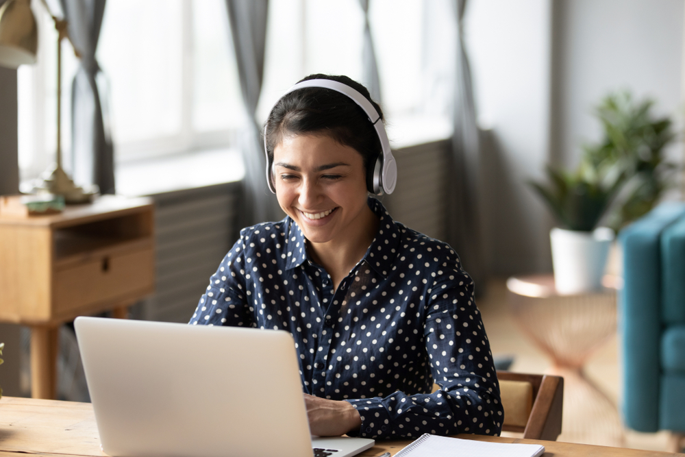 Happy young girl student wear headphone watch webinar listen online course communicate by conference video call e learn language in app laugh study with teacher lesson look at laptop at home