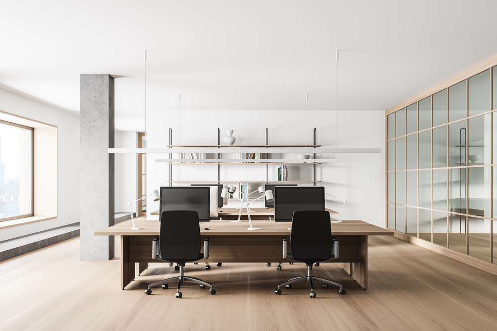 Interior of modern open space office with white and gray walls, wooden floor and big computer tables. 3d rendering