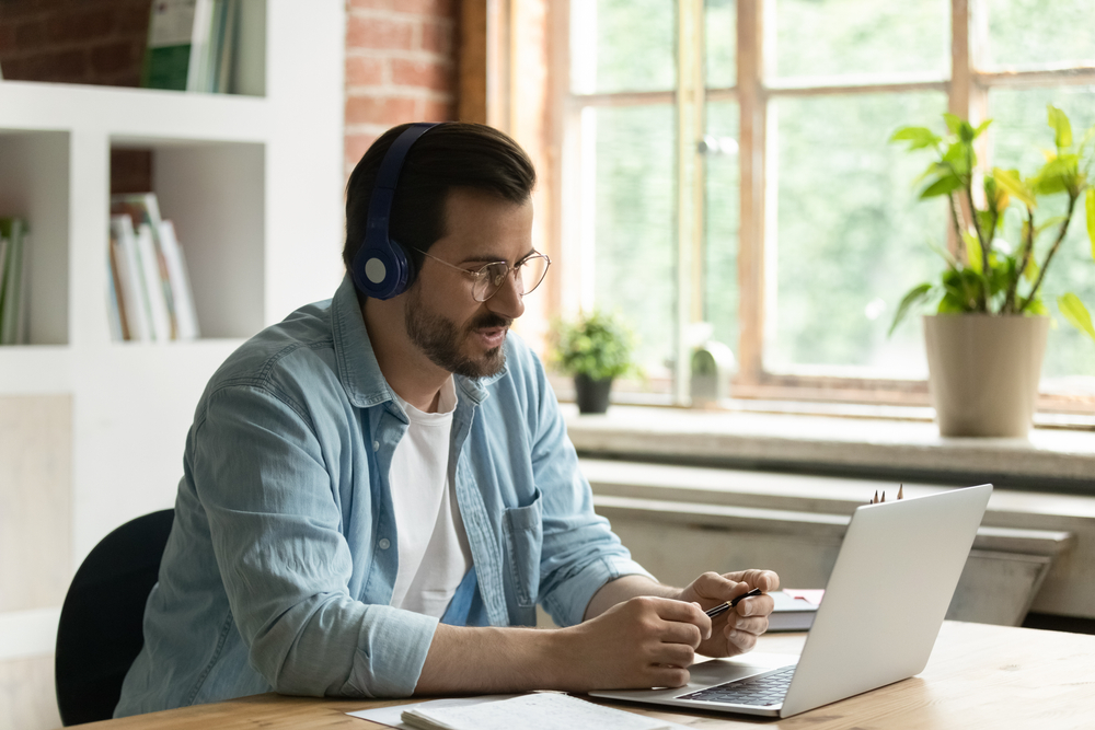Young Caucasian businessman in earphones work on computer online talk speak on video call with client. Male employee in headphones use laptop have webcam digital conference with customer