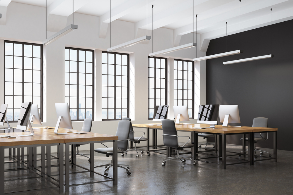 Side view of an open space office with a black wall, many tables with computers on them and a concrete floor. 3d rendering